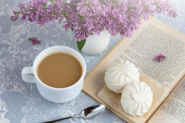 Kaffee oder tee mit milch und marshmallows. ein buch im garten mit einer tasse kaffee lesen. romantisches stillleben mit lila blumen.