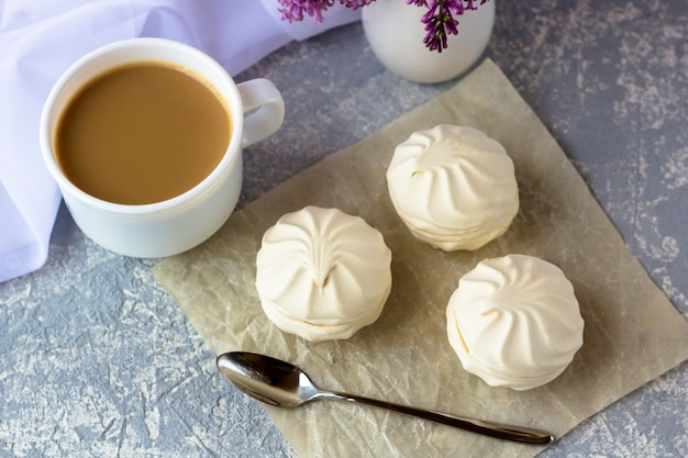 Kaffee oder tee mit milch und marshmallows. romantisches stillleben mit lila blumen. kaffeepause an einem frühlingstag im garten