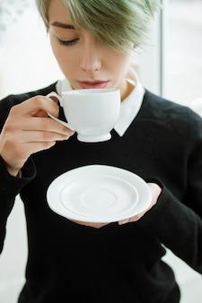 Kaffee- oder teegenuss. frau genießt eine tasse heißes getränk mit einer untertasse.