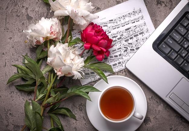 Kaffee, pfingstrosen und laptop auf grauem weinlesehintergrund