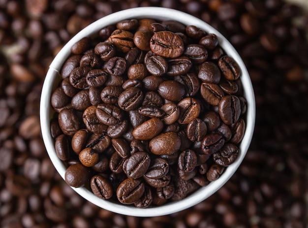 Kaffee-recycling-tasse zum mitnehmen mit gerösteten kaffeebohnen auf kaffeebohnenhintergrund. draufsicht.