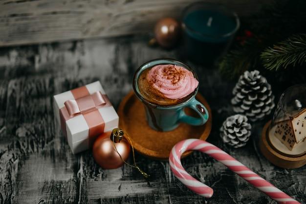 Kaffee, rosa eibisch, tannenzweig, tannenzapfen, geschenkbox, zuckerstange auf dunklem hintergrund.