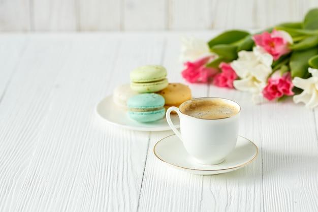 Kaffee, rosa und weiße tulpen und macarons auf dem weißen holztisch. frühstück. kaffeepause.