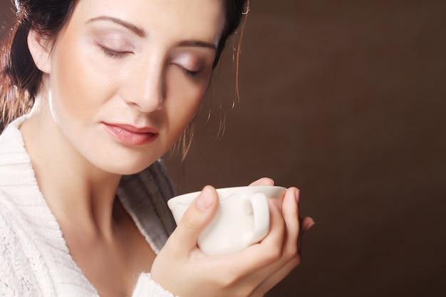 Kaffee. schönes mädchen, das tee oder kaffee trinkt. tasse heißes getränk