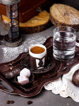 Kaffee serviert mit türkischen köstlichkeiten und einem glas wasser