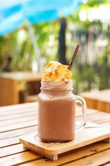 Kaffee smoothie auf einem holztisch- und betriebshintergrund.
