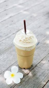 Kaffee smoothie und plumeriablume auf einem holztisch.