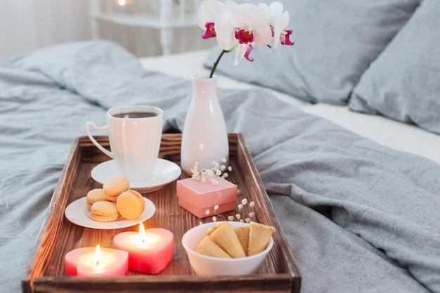 Kaffee, süßigkeiten, kerzen, blumen und kleid auf holztablett auf dem bett. konzept mit valentinstag