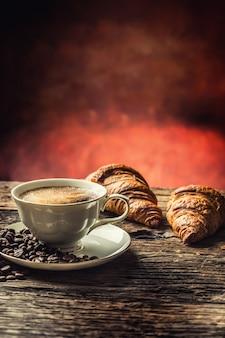 Kaffee. tasse kaffeecroissants und kaffeebohnen. vintage tasse und alter eichentisch.