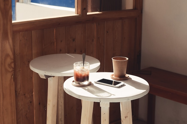 Kaffee, telefon und squash auf dem coffeeshop-tisch