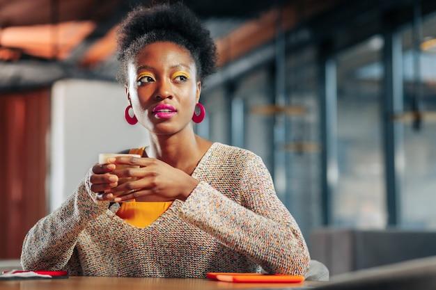 Kaffee trinken darkyed freelancer trägt rosa ohrringe und trinkt kaffee in gemütlicher cafeteria