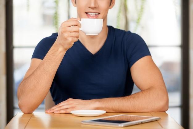 Kaffee trinken im restaurant. abgeschnittenes bild eines fröhlichen jungen mannes, der im restaurant kaffee trinkt und lächelt, während das digitale tablet auf dem tisch liegt