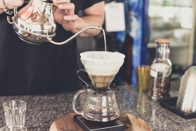 Kaffee tropft, barista gießt wasser auf kaffeemasse mit filter