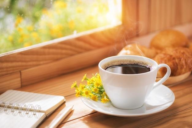 Kaffee und blumen zum frühstück am fenster mit morgensonnenlicht platziert