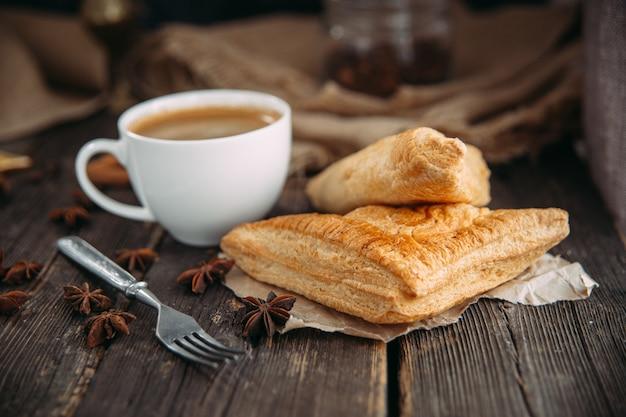 Kaffee und croissant auf dem holztisch.