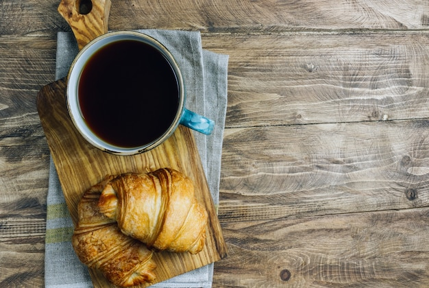 Kaffee und croissant auf rustikalem holztisch. französisches frühstück. draufsicht.