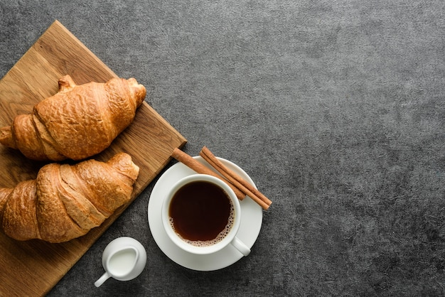 Kaffee und croissants auf einem rauen hintergrund mit kopienraum. flache zusammensetzung mit einer tasse kaffee und croissants.