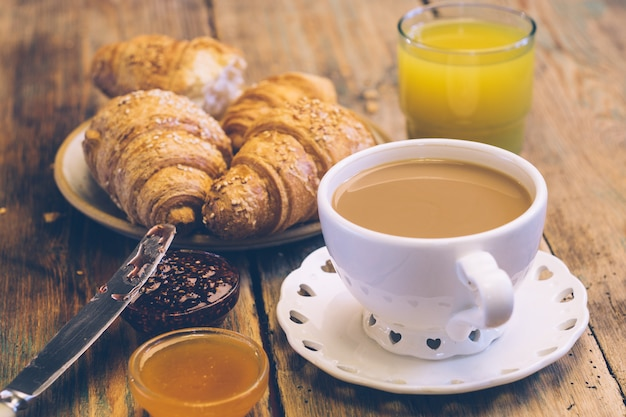 Kaffee und croissants mit marmelade und orangensaft. typisches französisches frühstück (petit déjeuner)