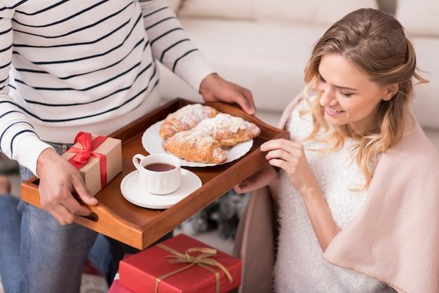 Kaffee und croissants. schließen sie oben von einem tablett mit leckerem leichtem frühstück, während sie in den händen eines hübschen jungen fürsorglichen mannes sind