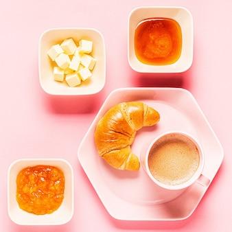 Kaffee und croissants zum frühstück auf einem rosa hintergrund, draufsicht,