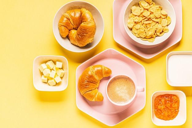 Kaffee und croissants zum frühstück auf gelbem grund, draufsicht, flache lage.