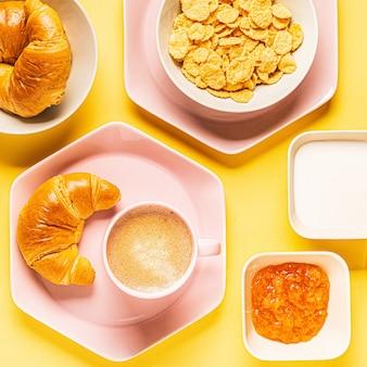 Kaffee und croissants zum frühstück auf gelbem hintergrund, draufsicht,