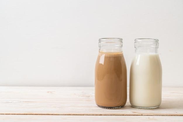Kaffee und frische milch in der flasche auf holz