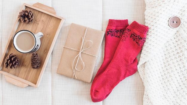 Kaffee und geschenk in der nähe von socken und pullover