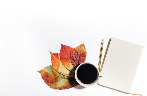 Kaffee und herbstblatt auf weißem hintergrund das konzept der herbstlichen gemütlichkeit