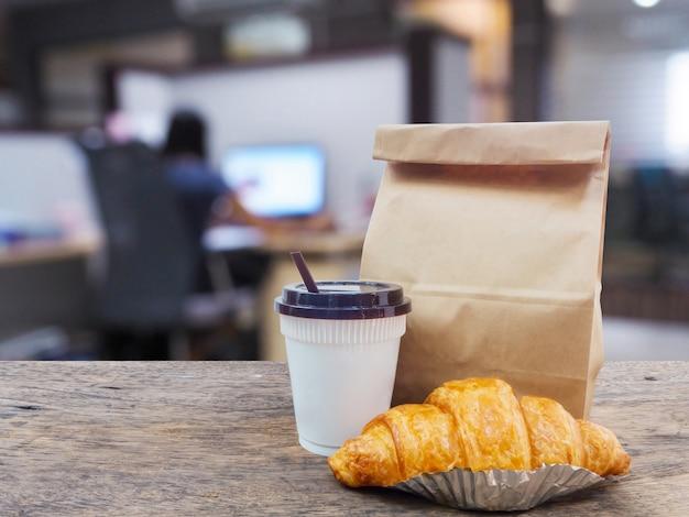 Kaffee und hörnchen mit papiertüte auf holztisch