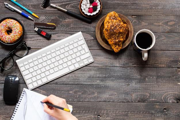 Kaffee und hörnchen zum frühstück auf rustikalem hölzernem hintergrund