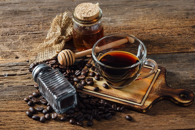 Kaffee und kaffeebohnen mit honig auf holztisch