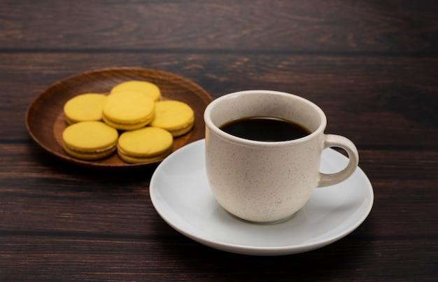 Kaffee und kekse in separaten tellern auf dunklen holzböden.