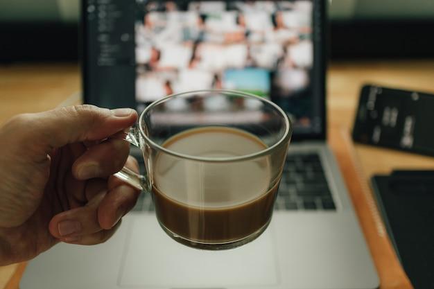 Kaffee und laptop am schreibtisch in warmem licht.