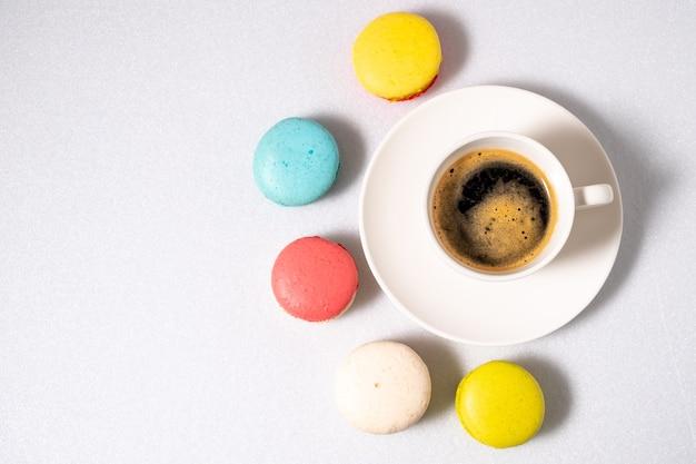 Kaffee und makronen auf einem weißen hintergrund. sicht von oben.