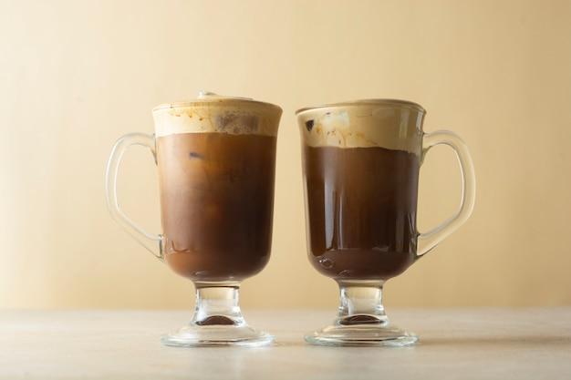 Kaffee und milch. leckere zwei kaffeegetränke mit eis, schlagsahne