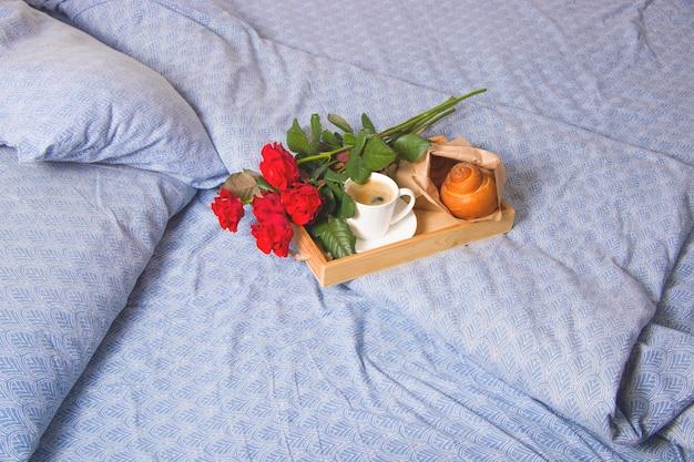 Kaffee und muffins auf einem hölzernen tablett. mit einem blumenstrauß auf dem bett.
