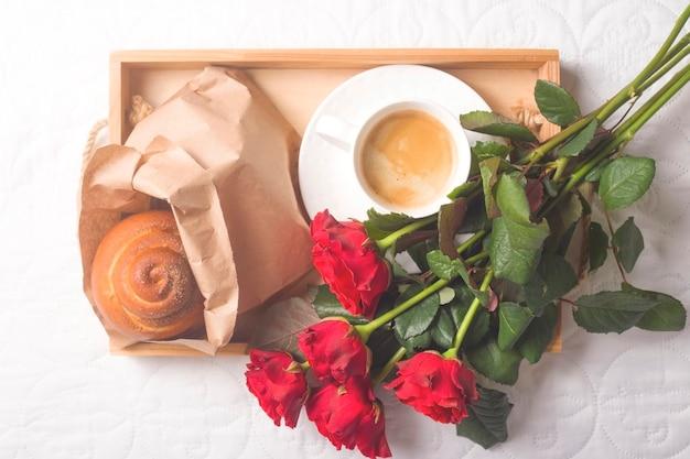 Kaffee und muffins auf einem holztablett. mit einem blumenstrauß auf dem bett.