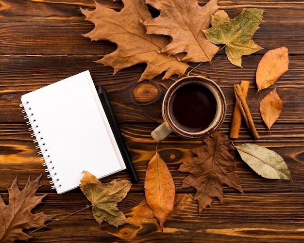 Kaffee und notizbuch auf hölzernem hintergrund