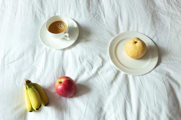 Kaffee und obst auf weißem bettlaken