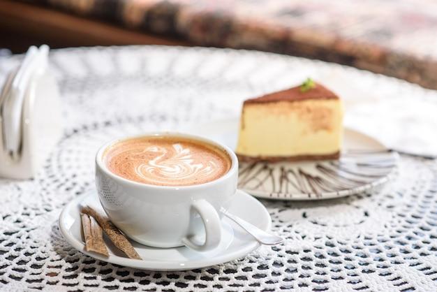 Kaffee und philadelphia-käsekuchen auf einem tisch in einer gemütlichen schokoladentafel. leckeres und einfaches essen.