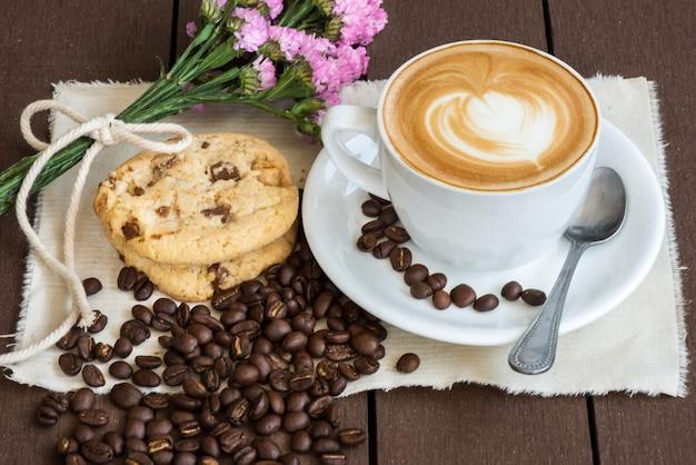 Kaffee und purpurrote blume witn bohne und weißes glas, teller, stoff auf braunem hölzernem