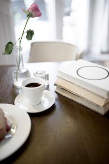 Kaffee und rose in der nähe von büchern