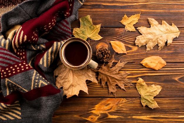 Kaffee und schal auf hölzernem hintergrund
