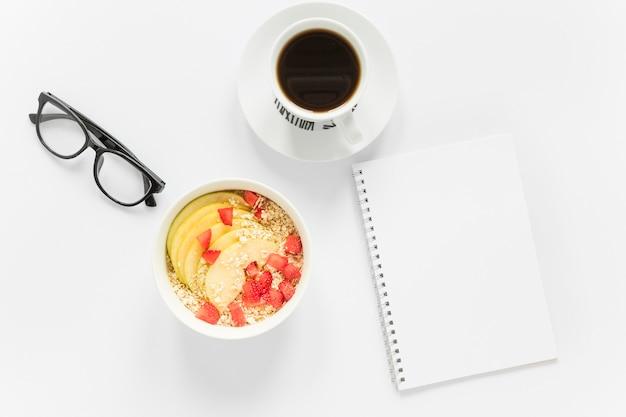 Kaffee und schüssel mit obst und müsli neben notizbuch