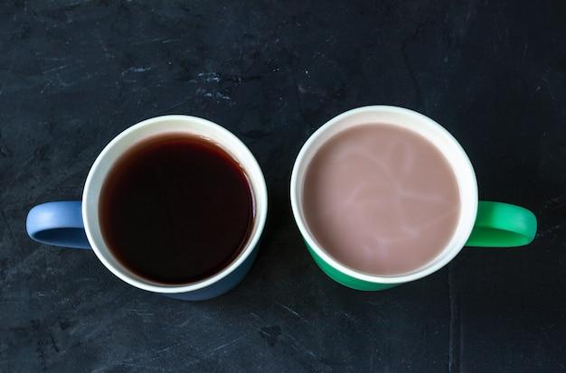 Kaffee und tee in den bechern auf dem hintergrund der hinteren tafel. kaffee gegen tee-konzept