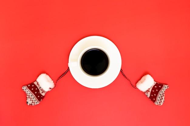 Kaffee und winterhandschuhe auf einem roten hintergrund.