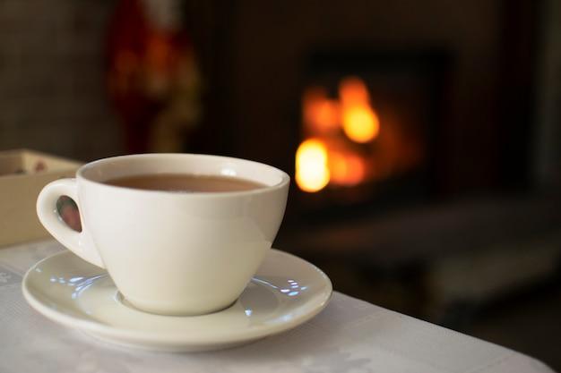 Kaffee, weiße tasse mit aromatischem kaffee auf einem kaminhintergrund