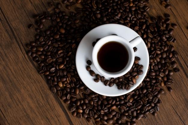 Kaffee, weiße tasse mit aromatischem kaffee, sahne, getreide, auf einem holztisch