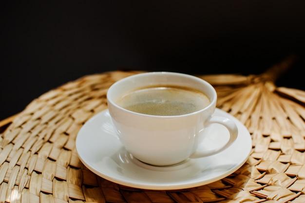 Kaffee, weiße tasse mit aromatischem kaffee, sahne, getreide, stroh servieren